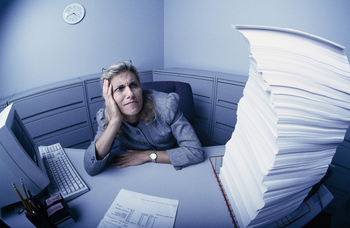 Business woman sitting at a desk with a computer and a large pile of papers