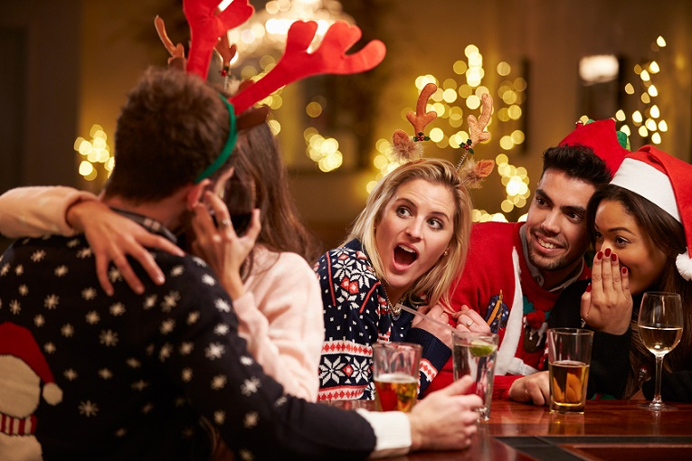 Couple Kissing In Bar As Friends Enjoy Christmas Drinks