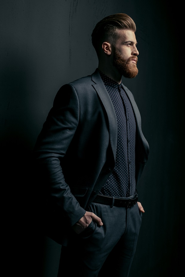 Stylish handsome bearded man in trendy suit looking away on black