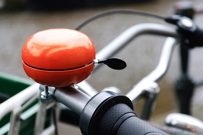 Bright orange bicycle bell. Shot was taken in Amsterdam, Holland.