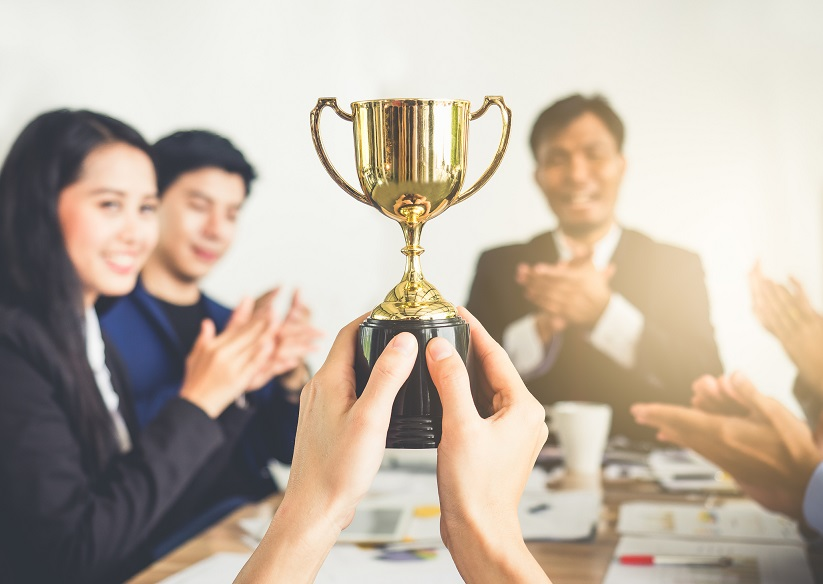 Businessman show thumbs up with trophy, reward, winner, champion and successful for business